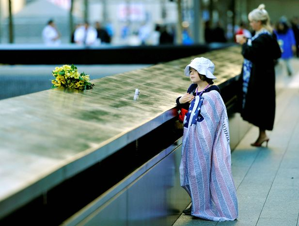 Ava Kathleen Schmoelzer, 7, from Stamford, Conn., places flowers for her aunt on the wall overlooking the South Tower reflecting pool on the 11th anniversary of the Sept. 11 terrorist attacks on the World Trade Ce