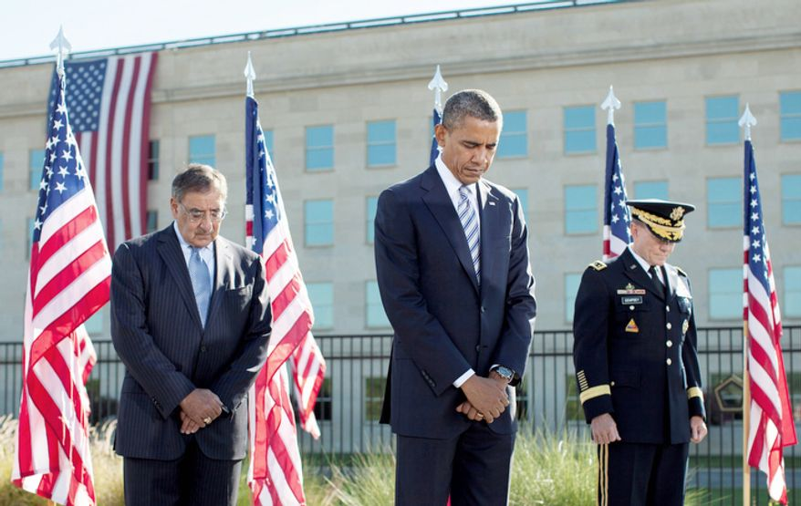 Presiden Obama, flanked by Defense Secretary Leon E. Panetta (left) and Gen. Martin Dempsey, bows his head at the Pentagon Memorial during a ceremony to mark the 11th anniversary of the Sept. 11 attacks. (AP Photo/Carolyn Kaster)