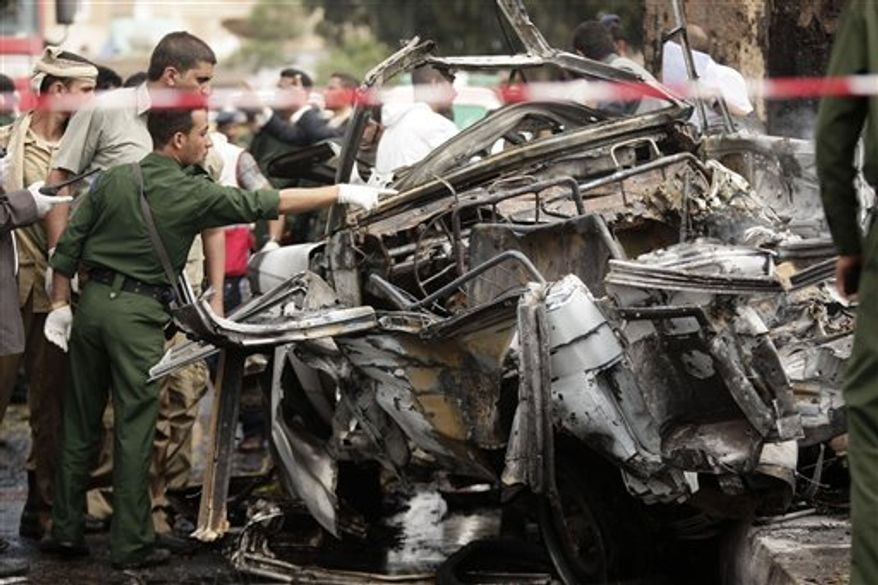 Forensic policemen collect evidence at the site of a car bomb attack targeting the motorcade of the country's defense minister in Sanaa, Yemen, Tuesday, Sept. 11, 2012. Yemeni officials say a car bomb targeting the motorcade of the country's defense minister has killed several people, but the minister escaped unharmed. (AP Photo/Hani Mohammed)