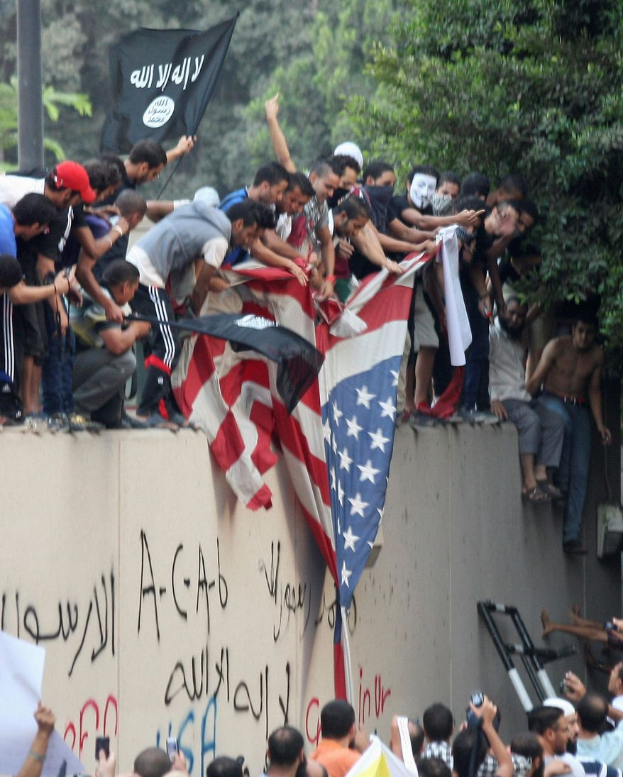 Protesters destroy an American flag pulled down from the U.S. Embassy in Cairo on Sept. 11, 2012. (Associated Press)