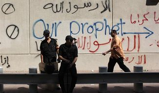"""Egyptian soldiers stand guard in front of the U.S. embassy in Cairo, Egypt, Wednesday, Sept. 12, 2012. An Israeli filmmaker based in California went into hiding after his movie attacking Islam's prophet Muhammad sparked angry assaults by ultra-conservative Muslims in Egypt. Arabic on the wall reads, """"anyone but God's prophet."""" (AP Photo/Nasser Nasser)"""