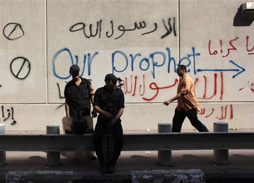 "Egyptian soldiers stand guard in front of the U.S. embassy in Cairo, Egypt, Wednesday, Sept. 12, 2012. An Israeli filmmaker based in California went into hiding after his movie attacking Islam's prophet Muhammad sparked angry assaults by ultra-conservative Muslims in Egypt. Arabic on the wall reads, ""anyone but God's prophet."" (AP Photo/Nasser Nasser)"