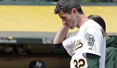 """In this photo from Wednesday, Sept. 5, 2012, Oakland Athletics pitcher Brandon McCarthy (32) places his hand to his head as he leaves the baseball game against the Los Angeles Angels in Oakland, Calif. McCarthy remains in a ''life-threatening'' situation in a Bay Area hospital two days after being hit in the head by a line drive. Struck on the right side of his head by a hard shot from the Angels' Erick Aybar, McCarthy suffered an epidural hemorrhage, brain contusion and skull fracture. He had two hours of surgery to relieve pressure on his brain late Wednesday night. A's athletic trainer Nick Paparesta was asked Friday if McCarthy was still in a life-threatening situation. """"Absolutely he is. It's brain surgery,'' Paparesta said. ''It's life-threatening. At any possible moment something could go wrong, he could have a complication. Absolutely.'' (AP Photo/Ben Margot)"""