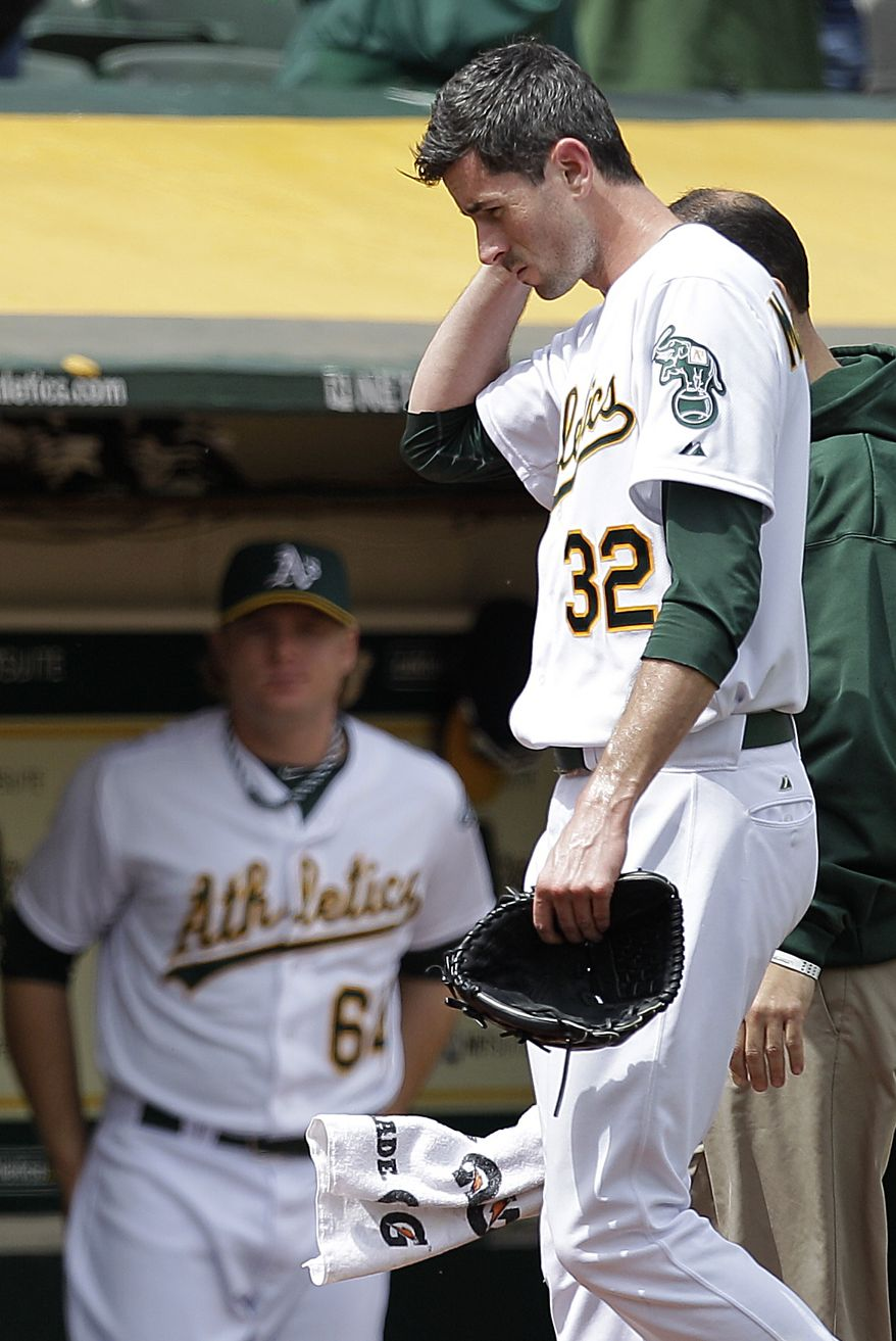 "In this photo from Wednesday, Sept. 5, 2012, Oakland Athletics pitcher Brandon McCarthy (32) places his hand to his head as he leaves the baseball game against the Los Angeles Angels in Oakland, Calif. McCarthy remains in a ''life-threatening'' situation in a Bay Area hospital two days after being hit in the head by a line drive. Struck on the right side of his head by a hard shot from the Angels' Erick Aybar, McCarthy suffered an epidural hemorrhage, brain contusion and skull fracture. He had two hours of surgery to relieve pressure on his brain late Wednesday night. A's athletic trainer Nick Paparesta was asked Friday if McCarthy was still in a life-threatening situation. ""Absolutely he is. It's brain surgery,'' Paparesta said. ''It's life-threatening. At any possible moment something could go wrong, he could have a complication. Absolutely.'' (AP Photo/Ben Margot)"