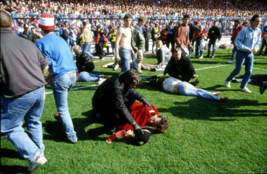**FILE** Police, stewards and supporters tend to wounded soccer supporters April 15, 1989, on the field at Hillsborough Stadium, in Sheffield, England. 96 Liverpool fans were crushed to death in the incident at the FA Cup semi-final match Liverpool against Nottingham Forest. (Associated Press)