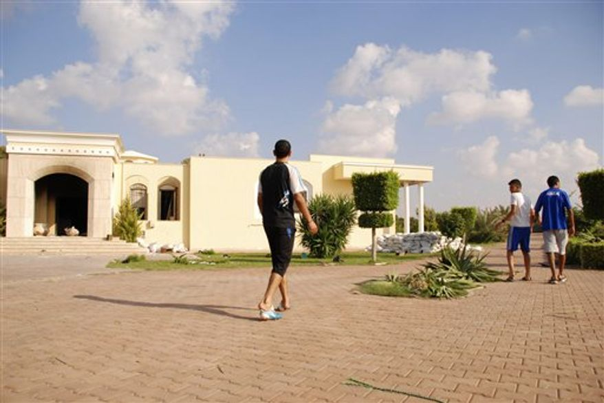 Libyans walk on the grounds of the U.S. consulate in Benghazi, Libya, after an attack that killed four Americans, including Ambassador Chris Stevens, Wednesday, Sept. 12, 2012. (AP Photo/Ibrahim Alaguri)