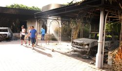 ** FILE ** Libyans walk on the grounds of the gutted U.S. Consulate in Benghazi, Libya, after an attack that killed four Americans, including U.S. Ambassador J. Christopher Stevens, on Wednesday, Sept. 12, 2012. (AP Photo/Ibrahim Alaguri)