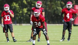 FILE - In this Aug. 2, 2012, file photo, Georgia running back Ken Malcome (24) gets ready for a drill during NCAA college football practice in Athens, Ga. Looking on are Kyle Karempelis (33) and Keith Marshall (4). Malcome and Merritt Hall are unlikely new starters in Georgia's backfield. The two will line up behind quarterback Aaron Murray when No. 6 Georgia opens its season against Buffalo on Saturday. (AP Photo/Daniel Shirey)