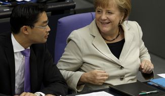 German Chancellor Angela Merkel (right) smiles as she talks with German Economy Minister Philipp Roesler during a budget debate in the Bundestag, the lower parliamentary house, in Berlin on Wednesday, Sept. 12, 2012. (AP Photo/Michael Sohn)