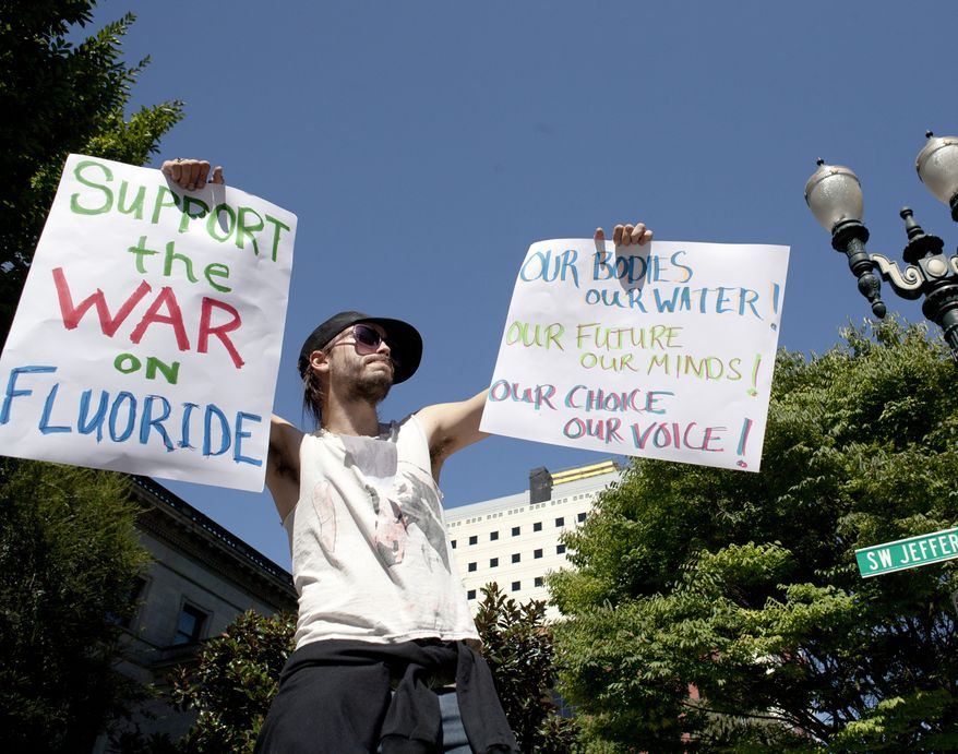 ** FILE ** Protester China Starshine demonstrates outside City Hall in Portland, Ore., on Thursday, Sept. 6, 2012, as the City Council opened public testimony on a plan to fluoridate the city's drinking water. (AP Photo/The Oregonian, Ross William Hamilton)
