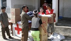 ** FILE ** North Koreans collect emergency goods, including kitchen sets and blankets, distributed by North Korean Red Cross officials in the flood-stricken city of Anju in the South Phyongan province of North Korea on Saturday, Aug. 4, 2012. (AP Photo/Kim Kwang Hyon)