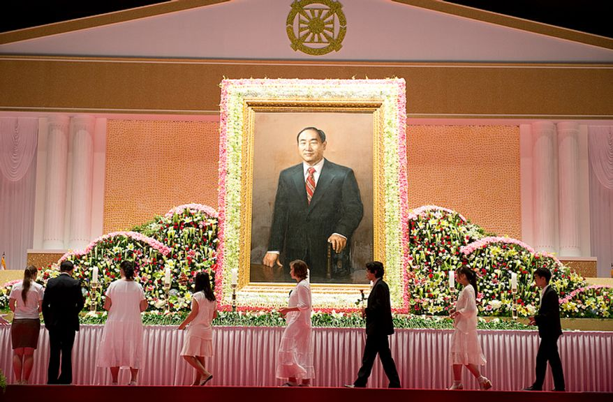 Mourners file past a portrait of the late Rev. Sun Myung Moon as they prepare to offer flowers in tribute to him at the Cheongpyeong Heaven and Earth Training Center complex near Seoul, Korea on Wednesday, Sept. 12, 2012. The 13-day memorial will culminate Saturday with a funeral service. Officials are expecting to completely fill the 30,000-person stadium. (Barbara L. Salisbury/The Washington Times)