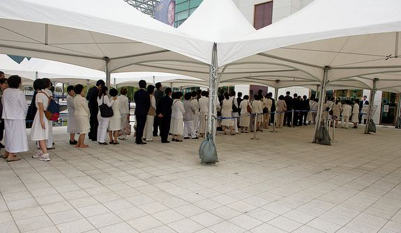 Mourners stand in line outside the Cheongpyeong Heaven and Earth Training Center complex outside of Seoul, Korea on Wednesday, Sept. 12, 2012 to pay tribute to the Rev. Sun Myung Moon. Traditional Korean funerals last three days, but the reverend's funeral will go for 13 days. It culminates Saturday, Sept. 15 with a SeongHwa Ceremony, which is considered the final farewell ceremony before burial. They are expecting some 30,000 people to attend. (Barbara L. Salisbury/The Washington Times)
