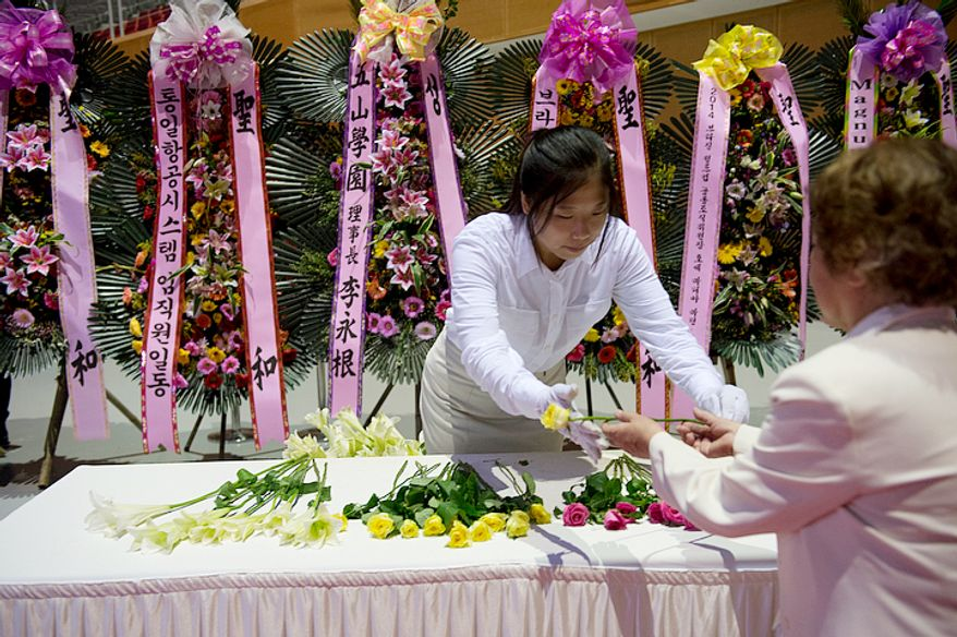 A volunteer hands a rose to a mourner at the Cheongpyeong Heaven and Earth Training Center complex on Wednesday, Sept. 12, 2012 so that the mourner can place it as an offering on a table beneath a portrait of the late Rev. Sun Myung Moon. Thousands of mourners have come to the complex near Seoul, Korea to pay their respects to the reverend, who founded the Unification Church. (Barbara L. Salisbury/The Washington Times)