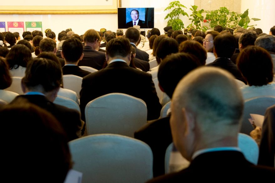 Mourners watch a video slideshow with photographs of the late Rev. Sun Myung Moon at the Cheongpyeong Heaven and Earth Training Center complex near Seoul, Korea on Wednesday, Sept. 12, 2012. Since thousands of mourners have come to pay tribute to the reverend, they ask them to watch this slideshow, then a video on the reverend's life and then go down to offer flowers and greet the family. This way the complex does not get overly crowded. They expect 30,000 to attend the funeral services on Saturday. (Barbara L. Salisbury/The Washington Times)