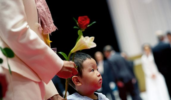 A young boy waits with his mother to place flowers on a table inside the Cheongpyeong Heaven and Earth Training Center complex outside of Seoul, Korea on Wednesday, Sept. 12, 2012 to honor the Rev. Sun Myung Moon. Mourners placed flowers (roses for the father and lilies for the mother) on a table and then bowed before family members. (Barbara L. Salisbury/The Washington Times)