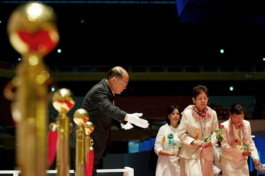 An usher shows mourners the way to place flowers (lilies for the mother and roses for the father) at a table inside the Cheongpyeong Heaven and Earth Training Center complex outside of Seoul, Korea in honor of the Rev. Sun Myung Moon on Wednesday, Sept. 12, 2012. Thousands of mourners have come to the complex to pay their respects for the founder of the Unification Church over the past several days. His 13-day funeral will culminate in a ceremony on Saturday in which some 30,000 are expected to attend. (Barbara L. Salisbury/The Washington Times)