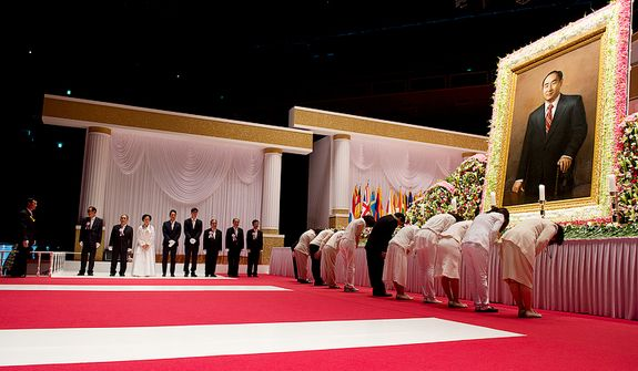 Family members of the Rev. Sun Myung Moon, including (in white) eldest daughter Ya-Jin stand at left waiting to greet mourners bowing at right after placing flowers on a table below a portrait of the reverend. The family members rotate throughout the day but are present from 8 a.m. to 10 p.m. to greet mourners as they come to the Cheongpyeong Heaven and Earth Training Center complex near Seoul, Korea to pay tribute to the late reverand, who founded the Unification Church. The official funeral service will be held this Saturday. This image was made Wednesday, Sept. 12, 2012. (Barbara L. Salisbury/The Washington Times)