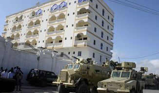 **FILE** African Union soldiers in armored personnel carriers keep guard Sept. 12, 2012, outside the Jazeera Hotel in Mogadishu, Somalia, the temporary home of new Somalian president Hassan Sheikh Mohamud, which was hit by two explosions earlier that day. The explosions came a day after the election of Mohamud, killing at least five people and wounded three others, witnesses and officials said. (Associated Press)