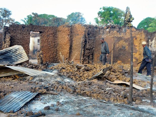 Residents observe the remains of their houses which were burned down during clashes in Chamwanamuma village, Tana River delta, north of Mombasa in Kenya Friday, Sept. 7, 2012. Fighting between a community of cattle herders and farmers over land and water killed 12 people there on Friday, the Kenya Red Cross said, adding that while the two communities periodically clash over resources this incident may also have politically instigated because it fits a pattern of violence which has occurred in three previous elections. (AP Photo)