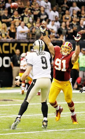 Redskins linebackers Ryan Kerrigan (91) and Brian Orakpo switched sides often to give Saints quarterback Drew Brees a variety of looks. (Associated Press)
