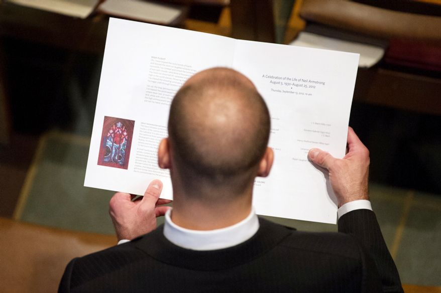 An attendee looks at the program booklet for the memorial service for Neil Armstrong at the National Cathedral. (Andrew Harnik/The Washington Times)