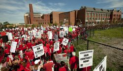 A large group of teachers marches past John Marshall Metropolitan High School on Wednesday, Sept. 12, 2012, in Chicago. (AP Photo/Sitthixay Ditthavong)