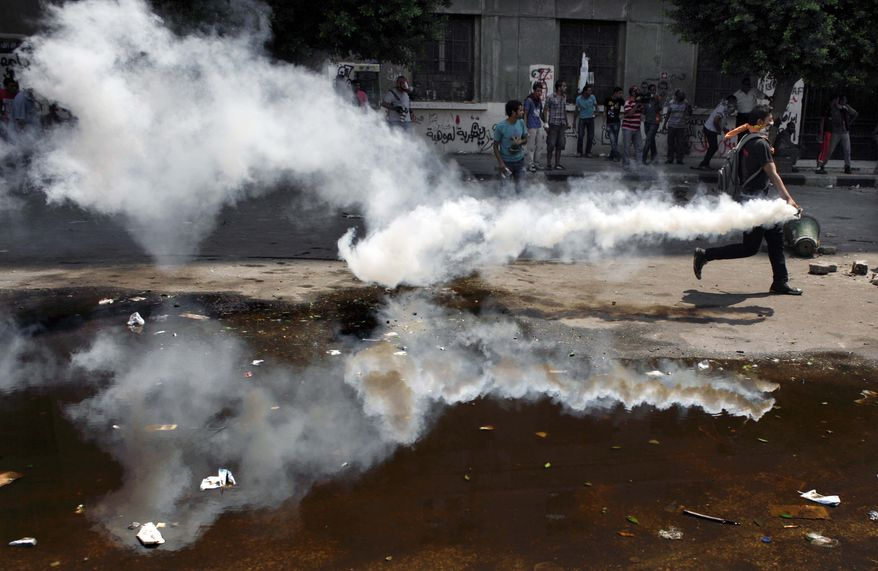 An Egyptian protester throws back a tear gas canister toward riot police, unseen, during clashes outside the U.S. embassy in Cairo, Egypt, Thursday, Sept. 13, 2012. Protesters clash with police near the U.S. Embassy in Cairo for the third day in a row. Police used tear gas to disperse the demonstrators and the two sides pelted each other with rocks. (AP Photo/Nasser Nasser)