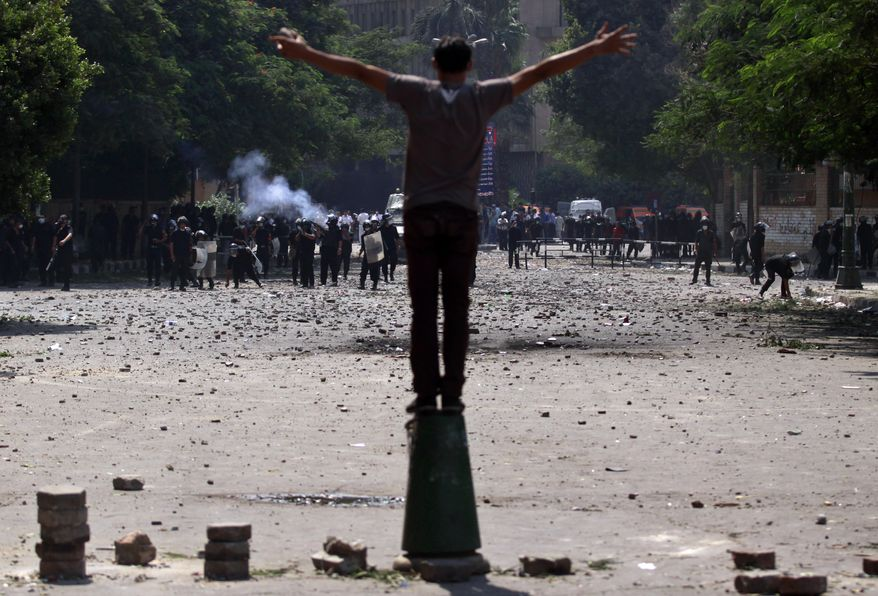 An Egyptian protester stands in front of the riot police during clashes near the U.S. embassy in Cairo, Egypt, Thursday, Sept. 13, 2012. Protesters clash with police near the U.S. Embassy in Cairo for the third day in a row. Egypt's Islamist President Mohammed Morsi vowed to protect foreign embassies in Cairo, where police were using tear gas to disperse protesters at the U.S. mission. (AP Photo/Khalil Hamra)