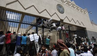 Yemeni demonstrators climb the gates of the U.S. Embassy in Sanaa, Yemen, on Thursday, Sept. 13, 2012, during a protest against a film ridiculing Islam's Prophet Muhammad. (Associated Press) ** FILE **