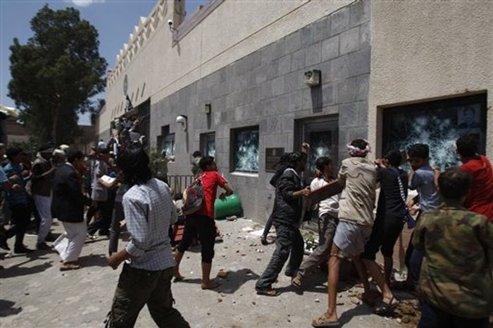 Yemeni demonstrators break windows of the U.S. Embassy during a protest about a film ridiculing Islam's Prophet Muhammad in Sanaa, Yemen, on Thursday, Sept. 13, 2012. (AP Photo/Hani Mohammed)