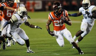 Virginia Tech running back Michael Holmes (20) looks for room against Georgia Tech's Rod Sweeting (6) and Quayshawn Nealy (54) during the first half of an NCAA college football game Monday, Sept. 3, at Lane Stadium, in Blacksburg, Va. Virginia Tech won in overtime,  20-17. (AP Photo/Don Petersen)