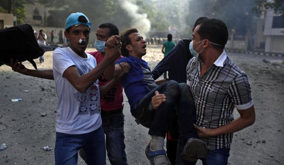 Egyptian protesters carry an injured man during clashes with riot police, unseen, near the U.S. embassy in Cairo, Egypt, Thursday, Sept. 13, 2012. Protesters clash with police near the U.S. Embassy in Cairo for the third day in a row. Egypt's Islamist President Mohammed Morsi vowed to protect foreign embassies in Cairo, where police were using tear gas to disperse protesters at the U.S. mission. (AP Photo/Khalil Hamra)