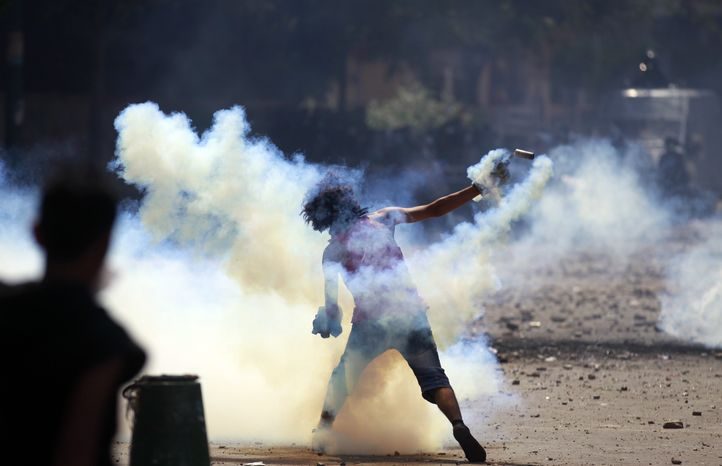 An Egyptian protester throws a tear gas canister toward riot police during clashes near the U.S. embassy in Cairo, Egypt, Thursday, Sept. 13, 2012. Protesters clash with police near the U.S. Embassy in Cairo for the third day in a row. Egypt's Islamist President Mohammed Morsi vowed to protect foreign embassies in Cairo, where police were using tear gas to disperse protesters at the U.S. mission. (AP Photo/Khalil Hamra)