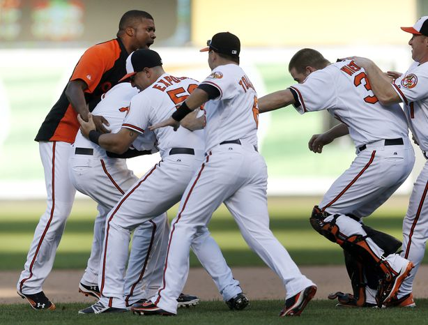 Members of the Baltimore Orioles celebrate with Manny Machado, second from left, after Adam Jones scored a run on Machado's single in the 14th inning of a baseball game in Baltimore, Thursday, Sept. 13, 2012. Baltimore won 3-2. (AP Photo/Patrick Semansky)