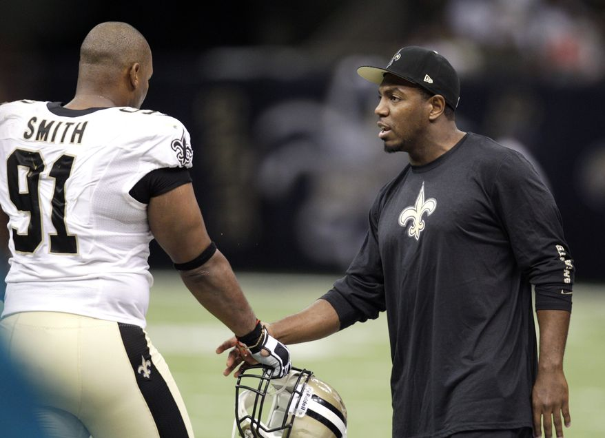 New Orleans Saints defensive end Will Smith (91) shakes hands with linebacker Jonathan Vilma in the second half of an NFL football game against the Washington Redskins at Mercedes-Benz Superdome in New Orleans, Sunday, Sept. 9, 2012.  The Saints won 40-32. (AP Photo/Matthew Hinton)