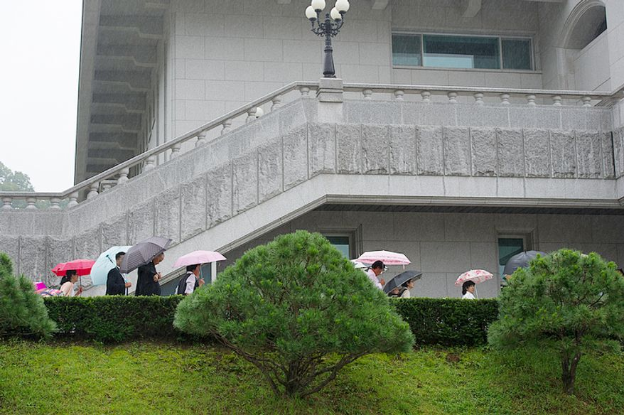 Mourners walk into the Cheongpyeong Heaven and Earth Training Center, where they are staying, at the Cheong Shim Peace World Center in Gapyeong-gun, Korea for the Rev. Sun Myung Moon's funeral. (Barbara L. Salisbury/The Washington Times)