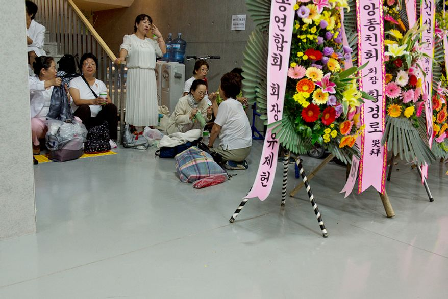 Volunteers and mourners take a break and rest in a stairway at the Cheong Shim Peace World Center in Gapyeong-gun, Korea on Thursday, Sept. 13, 2012. The complex has been open for days to allow mourners to come pay their respects to the late Rev. Sun Myung Moon, the founder of the Unification Church.  (Barbara L. Salisbury/The Washington Times)