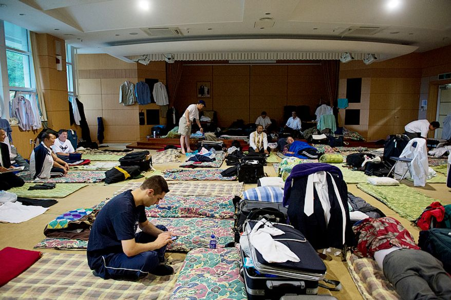 Men hang out in their makeshift dormitory, where they are sleeping on the floor in one of the rooms of the seminary at the Cheong Shim Peace World Center in Gapyeong-gun, Korea on Thursday, Sept. 13, 2012. Thousands of mourners who have come to pay tribute to the late Rev. Sun Myung Moon, the founder of the Unification Church, are sleeping on the floors in various buildings around the complex. (Barbara L. Salisbury/The Washington Times)