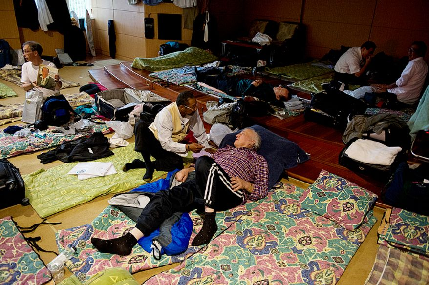Men hang out in their makeshift dormitory, where they are sleeping on the floor in one of the rooms of the seminary at the Cheong Shim Peace World Center in Gapyeong-gun, Korea on Thursday, Sept. 13, 2012.  (Barbara L. Salisbury/The Washington Times)