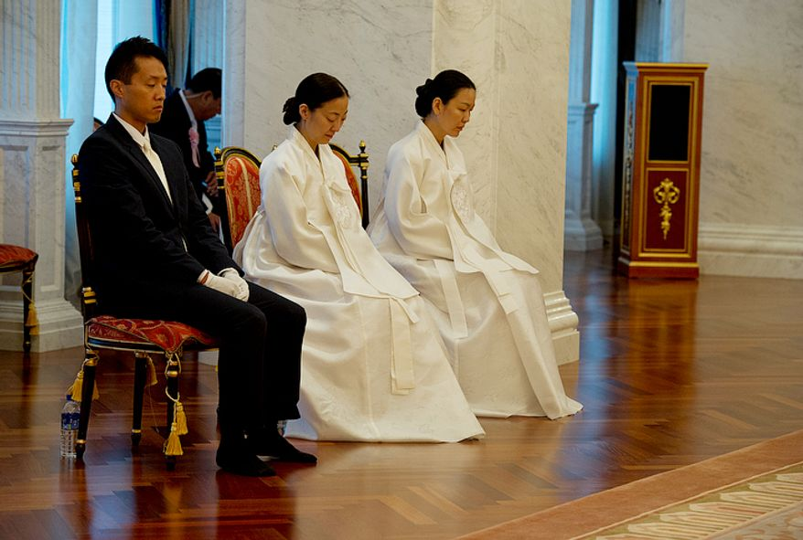 From left, Shin Bok Moon, Hoon Sook (Julie) Moon and Yeon-Ah Moon, all children of the late Rev. Sun Myung Moon, sit in a room in the palace where their father's body is on display in a glass-covered bier at the Cheong Shim Peace World Center in Gapyeong-gun, Korea on Thursday, Sept. 13, 2012. Mourners were invited to come pay tribute to the reverend and bow to his children. (Barbara L. Salisbury/The Washington Times)