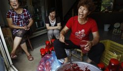 In this Aug. 21, 2012, photo, Lin, in red, sits with friends as they fill jars of red sorgum, a local delicacy, and talk about why they voted for the proposed casino to be built on Beigan in the Matsu island group, off northern Taiwan. (AP Photo/Wally Santana)