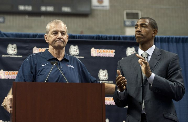 Connecticut head coach Jim Calhoun, left, reaches out to as Kevin Ollie, right, during a news conference announcing Calhoun's retirement, Thursday, Sept. 13, 2012,  in Storrs, Conn.  Ollie, an assistant coach under Calhou
