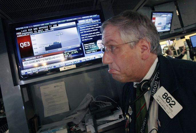 Trader Warren Meyers reacts to the announcement by the Federal Reserve as he watches a television screen on the floor of the New York Stock Exchange on Thursday, Sept. 13, 2012, in New York. (AP Photo/Richard Drew)
