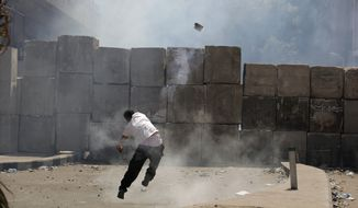 An Egyptian protester throws back a tear gas canister toward riot police Sept. 14, 2012, behind cement blocks that are used to close the street leading to the U.S. Embassy during clashes in Cairo as anger spread across the Muslim world about a film ridiculing Islam's Prophet Muhammad. (Associated Press)
