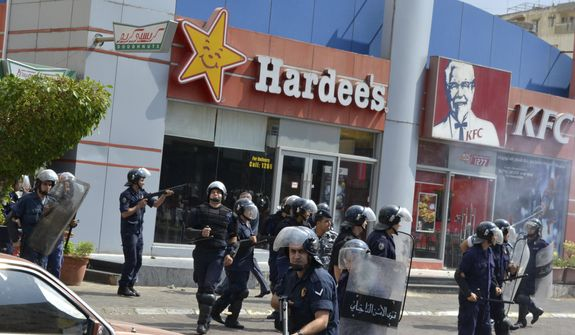 Lebanese riot police stand guard before a group of protesters, angry over the prophet film, attacked American fast food restaurants after Friday prayers, in the northeastern city of Tripoli, Lebanon, Friday Sept. 14, 2012. According to security officials no one was hurt in the attack which is part of widespread anger across the Muslim world about a film ridiculing Islam's Prophet Muhammad. (AP Photo)