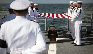 In this photo provided by NASA, members of the U.S. Navy ceremonial guard hold a United States flag over the remains of Apollo 11 astronaut Neil Armstrong during a burial at sea service aboard the USS Philippine Sea (CG 58), Friday, Sept. 14, 2012, on the Atlantic Ocean. Armstrong, the first man to walk on the moon during the 1969 Apollo 11 mission, died Aug. 25. He was 82. (AP Photo/NASA, Bill Ingalls)