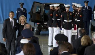 President Obama and Secretary of State Hillary Rodham Clinton walk Sept. 14, 2012, back to their seats after speaking during a ceremony at Andrews Air Force Base, Md., marking the return to the United States of the remains of the four Americans killed earlier in the week in Benghazi, Libya. Behind them at right is one of the flag draped transfer cases of the remains of the four Americans killed this week in Benghazi, Libya. (Associated Press)