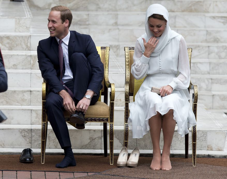 Prince William and his wife, Kate, the Duke and Duchess of Cambridge, take their shoes off before entering a mosque in Kuala Lumpur, Malaysia, on Sept. 14, 2012. (Associated Press)