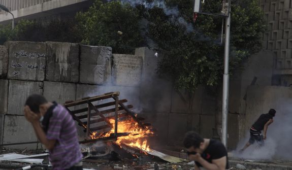 Egyptian protesters clash with security forces, unseen, near the U.S. embassy in Cairo, Egypt, Friday, Sept. 14, 2012, as part of widespread anger across the Muslim world about a film ridiculing Islam's Prophet Muhammad. (AP Photo/Khalil Hamra)